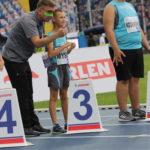 Uczniowei wraz z trenerem na lini startu biegu.
