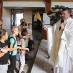 Wizerunek pierwszoklasistów oraz księdza w trakcie błogosławieństwa i święcenia placków.