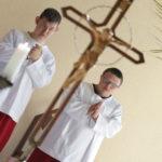 Wizerunek krzyża świętego oraz ministrantów.