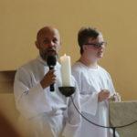 Wizerunek katechety i ministranta przy ołtarzu.
