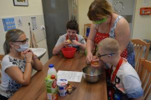 Uczniowie wraz z nauczycielem i wolontariuszem podczas przygotowania posiłku.