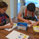 Uczniowie kolorujący ilustrację produktów spożywczych.