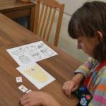 Uczennica wyklejająca pracę z wykorzystaniem symboli.