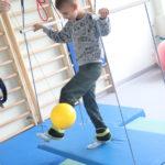 Uczeń podczas ćwiczeń w pozycji stojącej na platformie terapeutycznej.