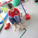 Chłopiec podczas ćwiczenia koordynacji z wykorzystaniem deskorolki.