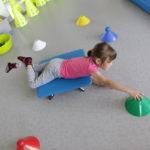 Dziewczynka ćwicząca na desce rotacyjnej.