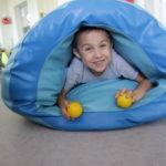 Chłopiec podczas aktywności z wykorzystaniem tunelu sensorycznego.
