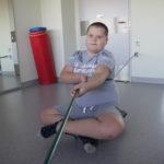 Uczeń ćwiczący na deskorolce z liną w pozycji siedzącej