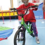 Młody Sportowiec podczas jazdy na rowerze biegowym.