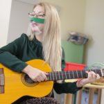 Nauczycielka k. I grająca na gitarze podczas jednego z punktów programu uroczystości.