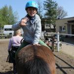 Uczeń podczas ćwiczenia jazdy tyłem na koniu.