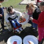 Grupa dzieci wraz nauczycielką podczas segregacji końskich przysmaków.