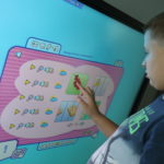 Uczeń wykonujący ćwiczenie logopedyczne z wykorzystaniem tablicy interaktywnej.