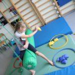 """Dziewczynka podczas ćwiczenia koordynacji wzrokowo-ruchowej na huśtawce """"wałek""""."""