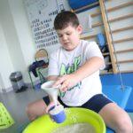 Uczeń podczas zabawy materiałami sypkimi na platformie terapeutycznej.