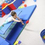 Dziewczynka podczas ćwiczeń na platformie terapeutycznej.