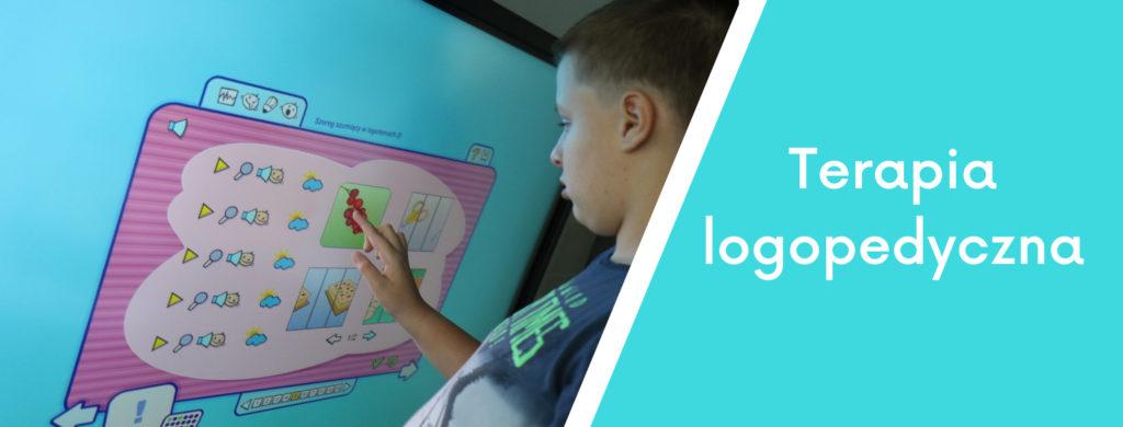 Uczeń wykonujący ćwiczenie logopedyczne na tablicy interaktywnej oraz napis terapia logopedyczna.