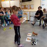 Przedszkolak podczas dopasowywania tematycznych etykiet do przedmiotów.