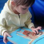 Dziewczynka podczas aktywności terapeutycznej wykorzystaniem tematycznej książeczki o piesku.