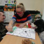 Podopieczny wraz z terapeutą i psem podczas wykonania portretu psa.