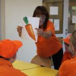Prowadząca spotkanie prezentująca uczestnikom ilustrację marchewki.