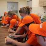 Uczestnicy spotkania podczas krojenia marchewek.