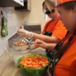 Uczennica wraz z nauczycielką podczas przygotowywania soku marchewkowego.