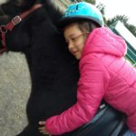 Uczennica przytulająca się do szyi konia.