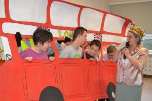 """Uczniowie oraz prowadzącą imprezę """"królową Elżbietą"""" z makietą londyńskiego autobusu."""
