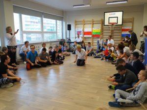Zdjęcie uczniów oraz gości ppodczas wspólnych zajęć muzycznych.