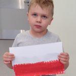 chłopeic trzymający wykonaną przez siebie flagę Polski.
