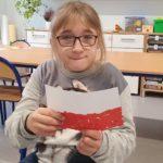 Uczennica trzymająca wykonaną przez siebie flagę Polski.