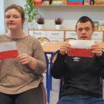 Podopieczni prezentujący wykonane przez siebie flagi Polski.