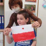Chłopiec wraz z nauczycielem trzymający flagę Polski.