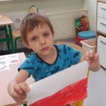 Chłopiec trzymający wykonaną przez siebie flagę Polski.
