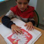 Chłopiec wyklejający godło Polski z gotowych elementów.