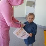 Wychowawca w przebraniu misia wręczający dziewczynce dyplom.
