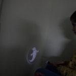 """Chłopiec obserwujący cień na ścianie """"duszek""""."""
