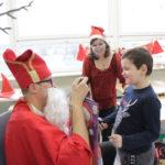 Przedszkolak w asyście wychowawczyni odbierający prezent od Mikołaja.