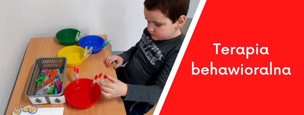 Chłopiec przypinający klamerki wg zadanego koloru oraz napis terapia behawioralna.