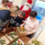 Grupa uczniów w towarzystwie Mikołaja otwierająca jedną z podarownych paczek.