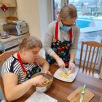 Uczennica wraz z wolontariuszką podczas przygotowywania świątecznych ciasteczek.