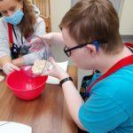 Uczeń wraz z wolontariuszką podczas przygotowywania świątecznych ciasteczek.