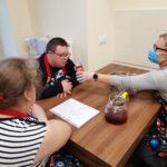 Wolontariuszka oraz uczniowie podczas doświadczania zapachu przyprawy - goździków.