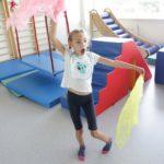 Dziewczynka podczas ćwiczeń ramion z wykorzystaniem chust.