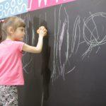 Dziewczynka zmazująca krędę z tablicy za pomocą gąbki.