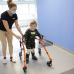 Chłopiec wraz z fizjoterapeutką podczas nauki chodu z wykorzystaniem kominezonu Dunag oraz czterokołowego chodzika.