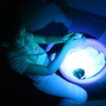 Uczennica manipulująca podświetlonym piaskiem kinetycznym.