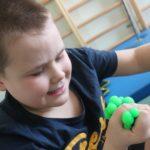Uczeń podczas manipulacji zabawką rozwijającą siłę mięśni dłoni.