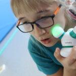 Uczennica masująca twarz masażerem elektrycznym.